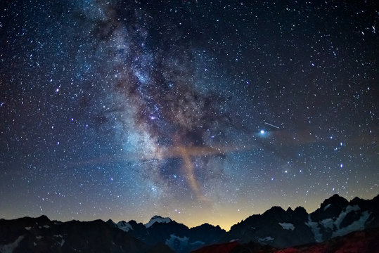 The Milky Way arch starry sky on the Alps, Massif des Ecrins, Briancon Serre Chevalier ski resort, France. Panoramic view high mountain range and glaciers, astro photography, stargazing