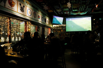 People watch the television broadcast of the soccer match between Arsenal and Everton inside a sports bar in Beijing