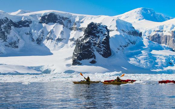 Kajak fahren in der Antarktis mit Eisberge im Hintergrund