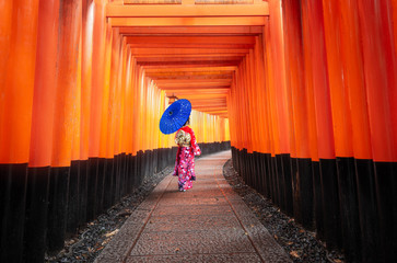 Red Torii gates with woman in kimono holding Blue umbrella at Fushimi Inari,Japan.