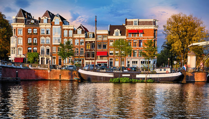 Fototapete - Amsterdam, Netherlands. Floating House and houseboat at channels by banks. Traditional dutch dancing houses among trees. Evening autumn street above water pink sunset sky with clouds.
