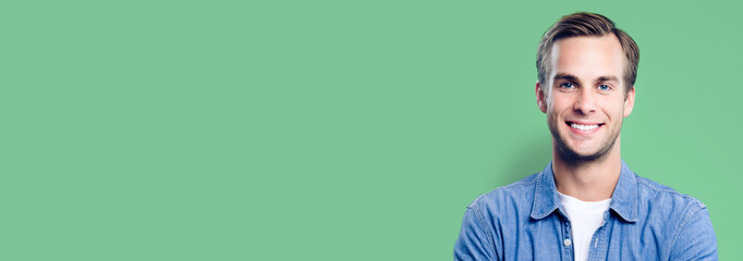 Portrait of happy man, with empty copy space area for slogan, advertising or text message, against green background. Caucasian male model in smart casual clothing, studio picture. Banner composition.