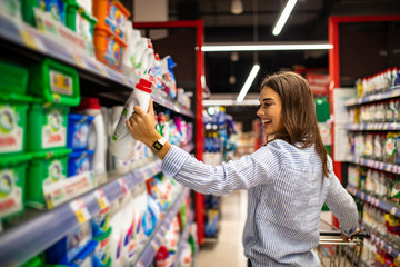 Casual woman choosing food from shelf in supermarket. Smiling customer standing near shelves. Beautiful young woman shopping in a grocery store/supermarket