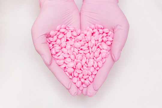 Wax for depilation of pink color. in hands in pink gloves in the shape of a heart. On white background. The concept of waxing, smooth skin.