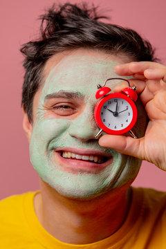 beautiful brunette man with alarm clock