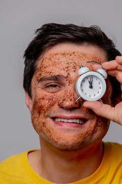 beautiful brunette man with coffee beans mask and alarm clock