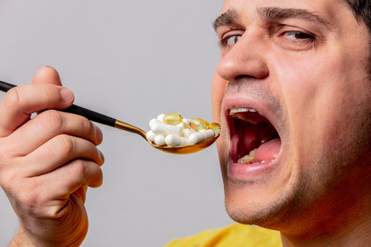 Man eats a pills with spoon