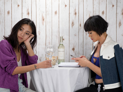 Two woman having wine one sad one busy