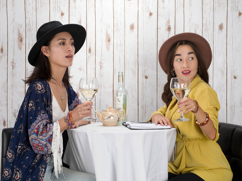Two woman wine looking at somone