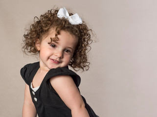 Smiling adorable toddler with curly brown hair cute expression isolated on background