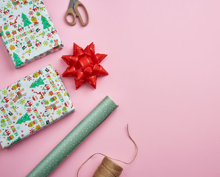rolls with wrapping paper, brown rope, scissors, decor and a wrapped square box with a gift