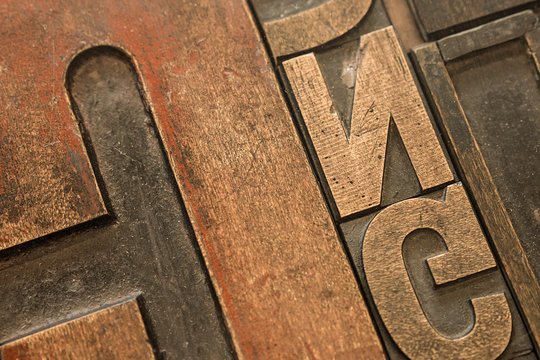 Close up of an arrangement of old wooden letterpress letter stamps.