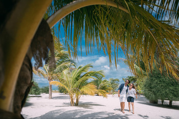 Fotobehang Palm boom A pair of lovers are walking on a tropical beach.