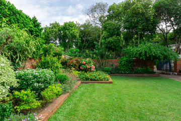 Beautiful English cottage garden, colorful flowering plant on smooth green grass lawn with orange brick wall and group of evergreen trees on background, in good care maintenance landscaping of a park