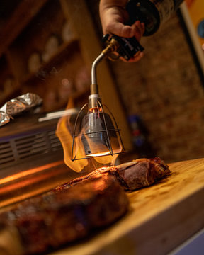 A home chef uses a blowtorch to sear a prime cut of steak