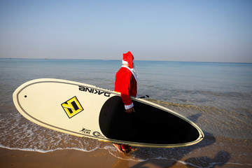 A man wearing a Santa Claus costume carries a SUP board as he walks into the Mediterranean Sea during an event organised by the Tel Aviv municipality, off the coast of Tel Aviv, Israel