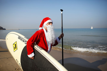 A man wearing a Santa Claus costume carries a SUP board as he walks on the beach near the Mediterranean Sea during an event organised by the Tel Aviv municipality, off the coast of Tel Aviv, Israel