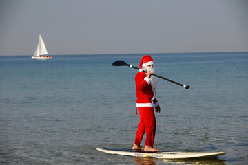 A man wearing a Santa Claus costume paddles on a SUP board in the Mediterranean Sea during an event organised by the Tel Aviv municipality, off the coast of Tel Aviv, Israel