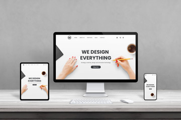 Wall Mural - Web design studio with multiple devices on office desk. Concept of responsive, flat web page design. Modern devices with thin edges on wooden desk