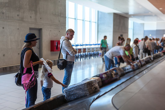 Family waiting their suitcase on baggage carousel in airport terminal
