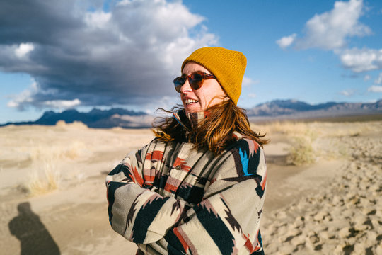 A young woman in a Native American patterned vintage jacket and mustard hat explores sand dunes in California