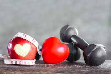 red apple with dumbbells ,measuring tape, sport diet and heart healthy concept  Fotobehang