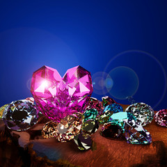 Fototapete - A heart shape diamond on a pile of colorful diamond on brown ground with flare.