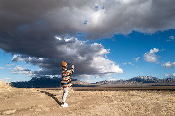 A young woman in a Native American patterned vintage jacket and mustard hat explores sand dunes in California under approaching storm clouds