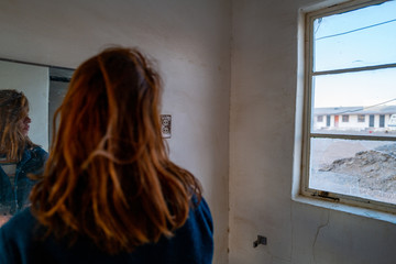 A red haired girl looks outside an abandoned motel bathroom window in a desert ghost town