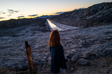A woman looks at a polluted waterway of industrial runoff in the desert