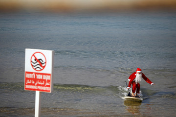 A man wearing a Santa Claus costume surfs on a SUP board in the Mediterranean Sea during an event organised by the Tel Aviv municipality, off the coast of Tel Aviv, Israel