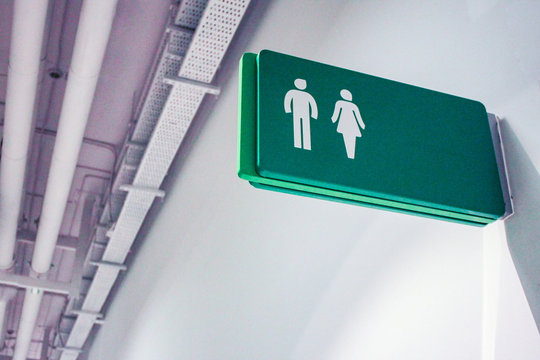 Public toilet sign for restroom with man and woman picture in green color on a white wall background