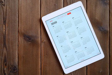 tablet with open calendar for 2020 year on a wooden background. space for text