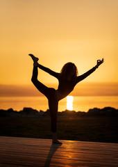 Foto op Plexiglas Rood Woman practicing yoga on the beach