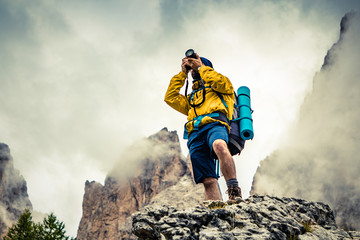 Young man hiker taking pictures on stone mountain with cloudy sky and fog. Yellow jacket, backpack, black beard and beanie. Traveling Dolomites, Italy.