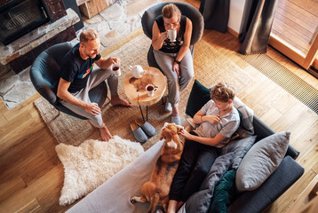 Cozy family tea time. Father, mother and son  at the home living room. Boy lying in comfortable sofa and  stroking their beagle dog and smiling. Peaceful family moments concept image.