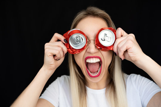 Screaming woman with red lips and cans holding on her face as glasses. Black background
