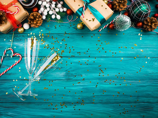 Christmas new year dark green background with festive ornament and gift boxes frame with champagne flutes full of golden star confetti. Holiday new year dinner lunch celebration concept