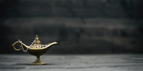 Aladdin Magic Genie Lamp on black wooden background