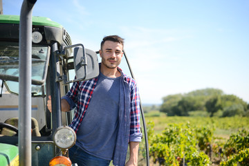 handsome man farmer in the field driving a tractor agriculture agronomy business equipment Fotomurales