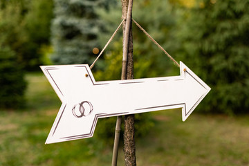 Arrow shaped white sign with an empty space for text on it. Placed in a green outdoor setting. Wedding Sign.