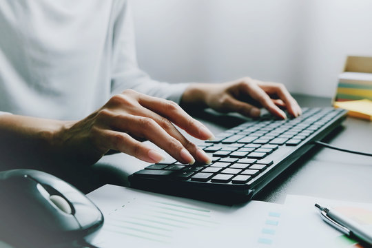 2 hands of Asian woman is press, typing on 2 language keyboard as Thai and English. Maybe preparation about information to report, chat to lover or shopping online by connect to internet at home, cafe