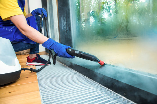 professional cleaning service. woman in uniform and gloves sponge washes panoramic windows in the cottage. washing steam mop and scraper