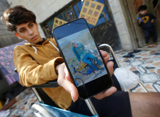 Hadi Ali an Iraqi demonstrator whose leg was amputated after clashes with Iraqi security forces, during ongoing anti-government protests, shows his picture by his mobile at his home in Basra