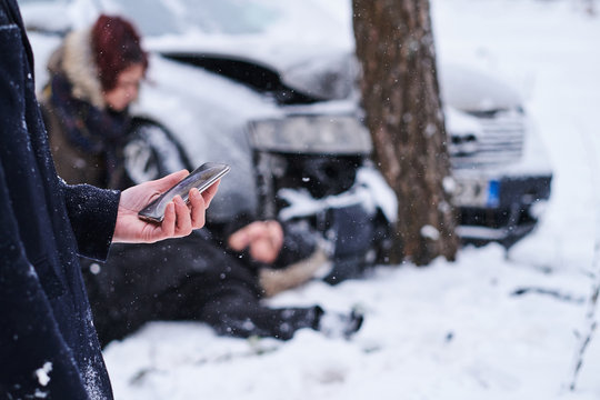 Car accident in winter forest, one man is injured, woman is checking him, and second man is calling 112.