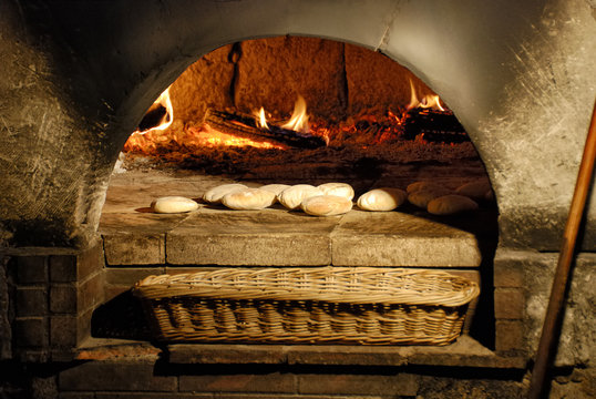 Traditional wood fired bread being placed into a super hot brick oven.