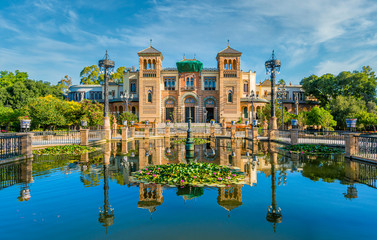 Museum of Popular Arts and Traditions reflecting in the near fountain in Seville, Andalusia, Spain. Fotomurales