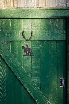 Porte en bois peinte en vert avec des reflets doré et fer à cheval
