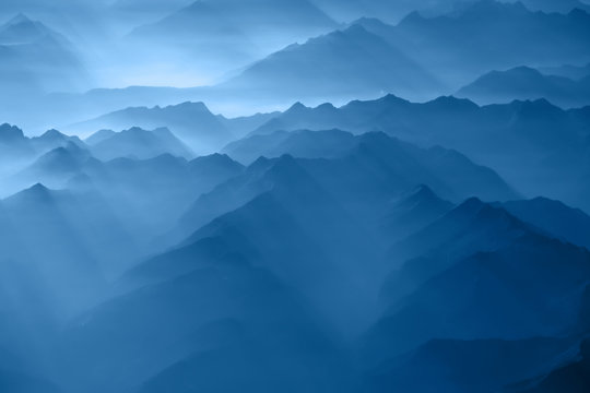 Fluffy clouds above Alp mountains, a view from airplane window. Color of the year 2020 classic blue toned. Soft focus