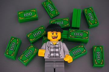Tambov, Russian Federation - December 04, 2019 Lego criminal against Lego money bricks on gray background. Studio shot.